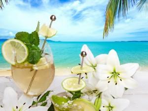 Bebidas frescas y flores junto al mar