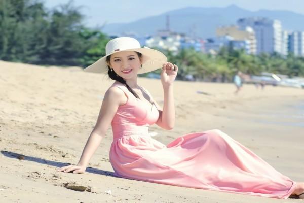 Bella mujer asiática sentada sobre la arena