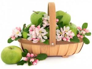 Una cesta con manzanas verdes y aromáticas flores