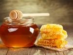 Frasco con miel y panal de abeja