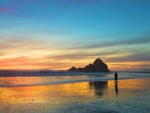 Postal: Una pareja contemplando el atardecer en la playa