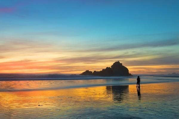 Una pareja contemplando el atardecer en la playa