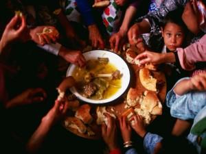 Postal: Manos con pan en torno a un plato de comida