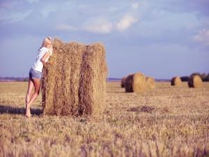 Una chica junto a un fardo de paja