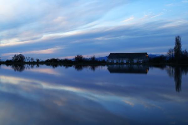Casa junto al lago con una luz encendida