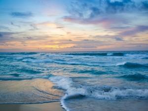 Postal: Las olas del mar formando espuma en la orilla