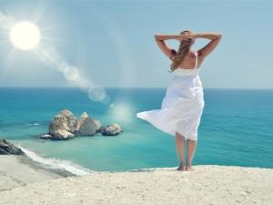 Un mujer contemplando el mar y los rayos del sol