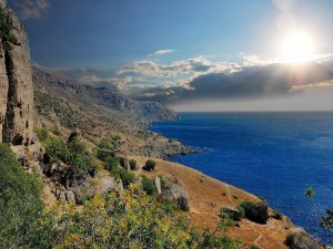 Postal: El sol iluminando la costa y el mar azul