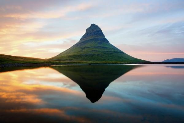 Montaña verde reflejada en el agua