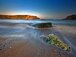 Agua de mar deslizándose por las piedras en la orilla