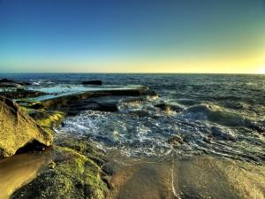 Postal: El sol iluminando las rocas y el mar