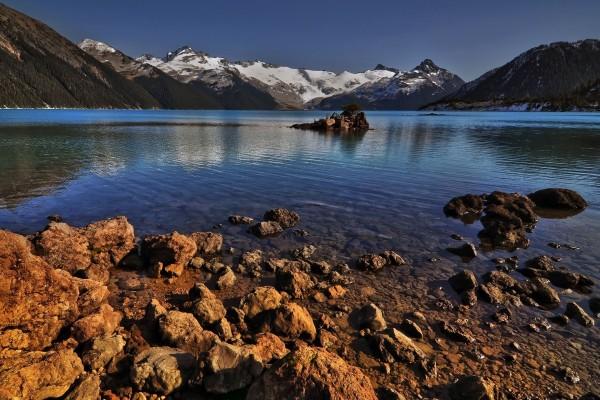 Montañas con nieve junto al lago
