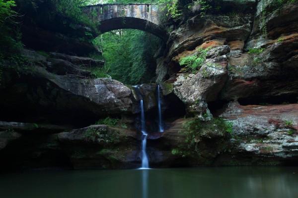 Una débil cascada bajo el arco del puente