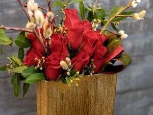 Recipiente con rosas rojas y ramas