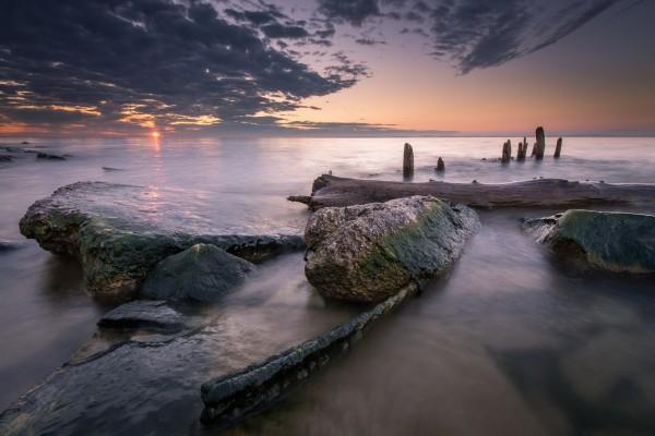 Grandes troncos y piedras en el mar