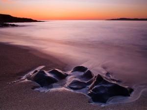 Piedras enterradas en la arena de la playa