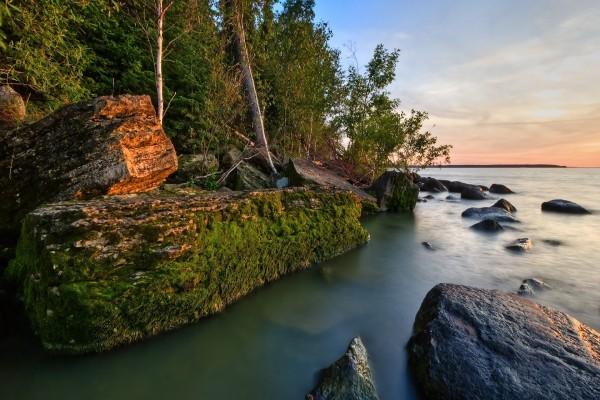 Grandes rocas cubiertas de musgo junto al agua