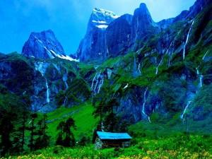 Postal: Cabaña entre inmensas montañas