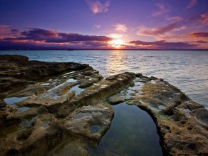 El sol tras las nubes iluminando el mar