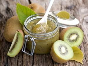 Kiwis recién cortados junto a un frasco de mermelada de kiwi