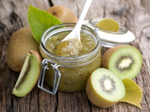 Postal: Kiwis recién cortados junto a un frasco de mermelada de kiwi