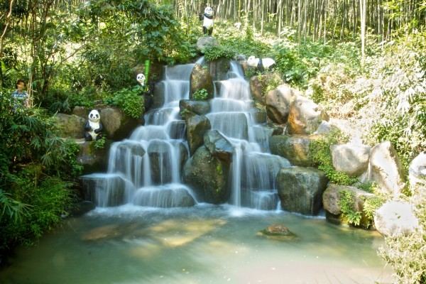 Estatuas de osos panda junto a la cascada