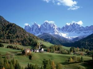Casas en un bonito valle verde junto a las grandes montañas