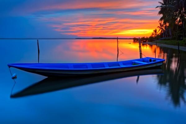 Un bote en el agua a la entrada del sol