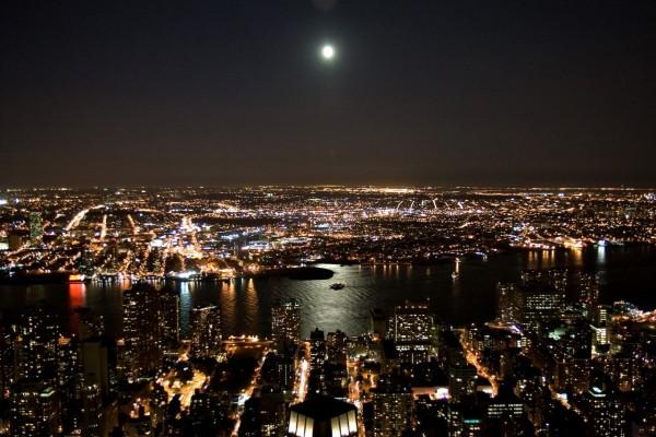 Luces y luna en la noche de una ciudad