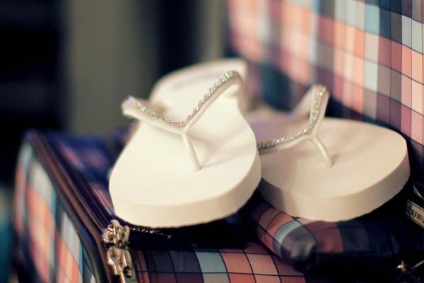 Sandalias blancas sobre las maletas