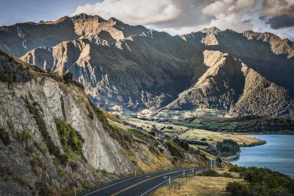 Carretera entre montañas y un lago
