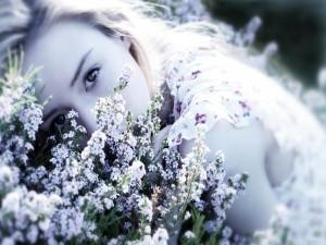 La mirada de una bella joven tumbada entre flores