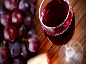 Postal: Copa de vino tinto junto a unas uvas negras