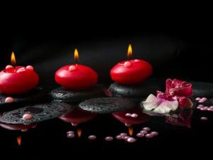 Guijarros, perlas y velas encendidas de color rojo