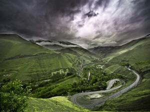 Postal: Una carretera con muchas curvas en las montañas