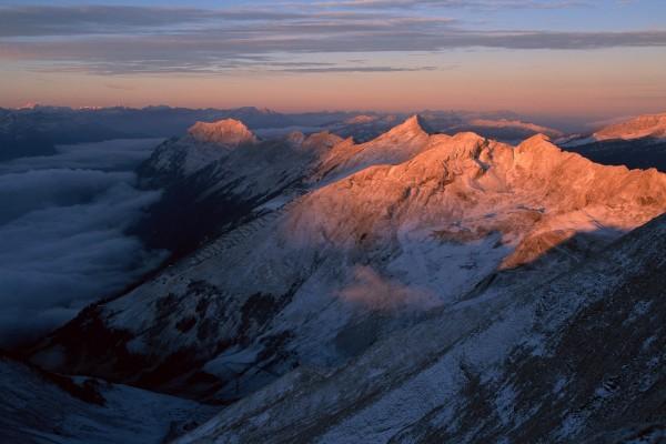 El sol iluminando grandes montañas