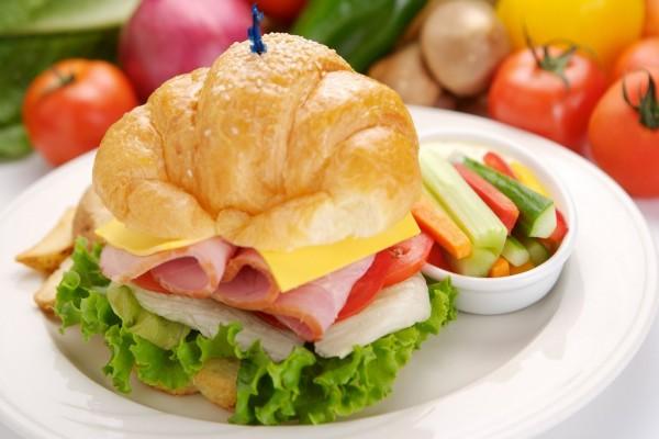 Un delicioso cruasán con queso, jamón, lechuga y tomate acompañado de unas crudités