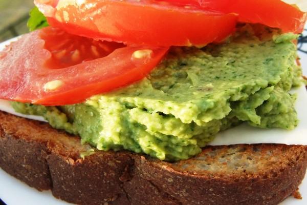 Rebanada de pan con guacamole, queso y tomate