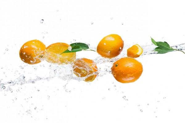 Naranjas enteras y cortadas en el agua