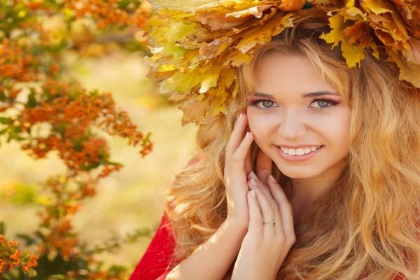Hermosa mujer con hojas otoñales adornando su cabeza