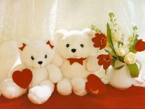 Dos tiernos osos de peluche junto a jarrón con flores