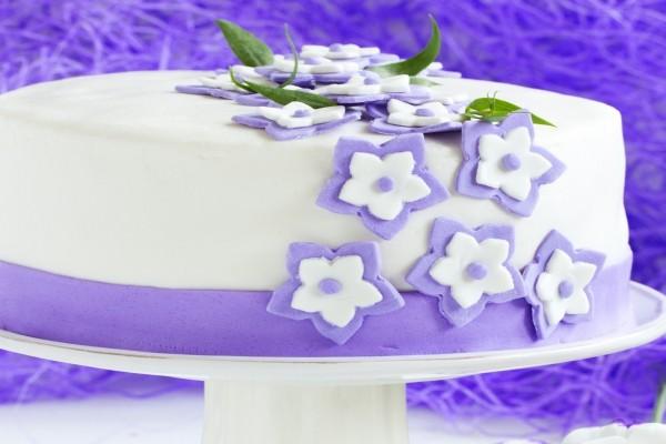 Una bonita tarta cubierta de fondant con pequeñas flores