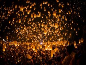 Personas soltando farolillos encendidos para que suban al cielo