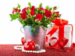 Postal: Arreglo floral con rosas rojas junto a una caja de regalo