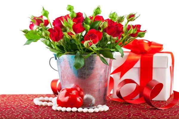 Arreglo floral con rosas rojas junto a una caja de regalo