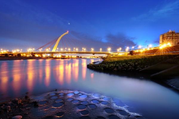 Un puente sobre el agua con brillantes luces al anochecer