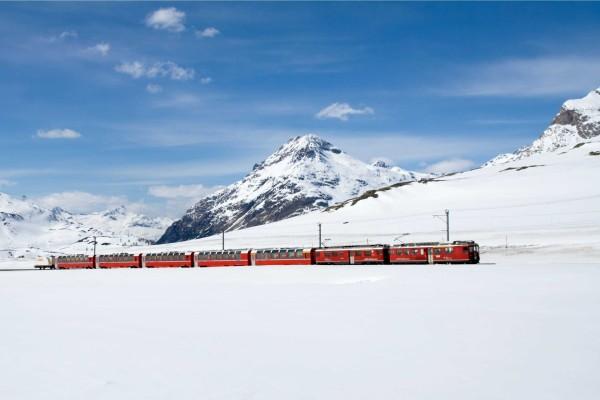Un tren rojo atravesando parajes cubiertos de nieve
