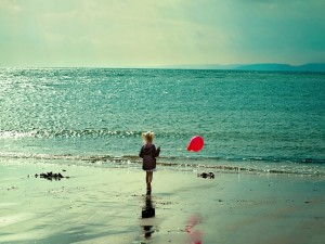 Postal: Niña con un globo en la playa