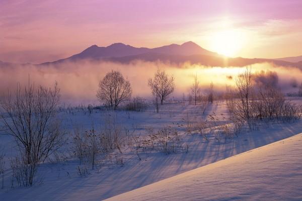 El sol al amanecer sobre un paisaje cubierto de nieve