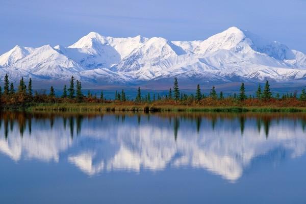Grandes montañas nevadas reflejadas en el agua